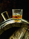 Whiskey in a glass with ice on an oak barrel of old using dramatic lighting Royalty Free Stock Images