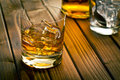 Whiskey in glass with ice on wooden table Royalty Free Stock Photos