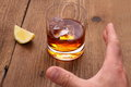 Whiskey with ice cubes in glass and grab hand close up Royalty Free Stock Photos