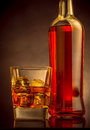 Whiskey with ice cubes in glass near bottle on black background, warm atmosphere Royalty Free Stock Photo