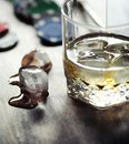 Whiskey with ice with a glass. Cubes of ice on a wooden table an
