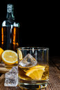 Whiskey with lemon and ice cubes on rustic wooden background Stock Photo