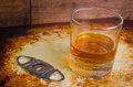 Whiskey neat with a cigar cutter rustic above rocks glass of in setting Stock Image