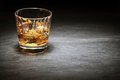 Whiskey on the rocks in a glass tumbler standing bar counter shadows with highlight over copyspace or place for Royalty Free Stock Images