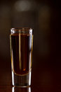 Whiskey shot closeup of a of served on a dark bar with an out of focus background Royalty Free Stock Photo