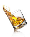 Whiskey splashing of out of glass isolated on white Stock Photos