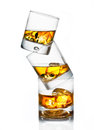 Whiskey three glasses of with ice one on top of the other on white background Royalty Free Stock Photo