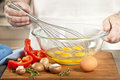 Whisking eggs in bowl closeup on man s hands for cooking omelet with vegetables Royalty Free Stock Images