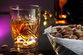 Whisky with almonds cup and glass of on dark purple background Stock Photography