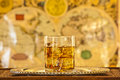 Whisky glass on silver platter on wooden table Royalty Free Stock Image