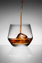 Whisky pouring on ice in glass Royalty Free Stock Photo
