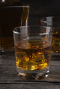 Whisky in two glasses on a dark wooden background Royalty Free Stock Photo