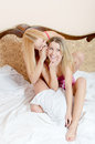 2 whispering: beautiful blond young women cute girlfriends having fun sitting together laughing in pajamas on white bed portrait Royalty Free Stock Photo