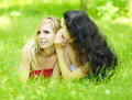 Whispering two girlfriends lying on grass Royalty Free Stock Photo