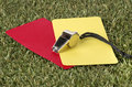 Whistle with red and yellow card on the field close up of Royalty Free Stock Photography