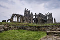 Whitby abbey england is a ruined benedictine overlooking the north sea on the east cliff above in north yorkshire it Royalty Free Stock Photos