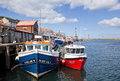 Whitby fishing boatd two small wooden boats docked in harbour Royalty Free Stock Photo