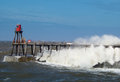Whitby pier in rough seas waves crashing over Stock Images