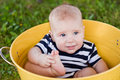 White 7-month-old baby in yellow bucket Stock Photos