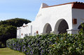 White adobe house mexican made of painted with tropical shrubbery and red tile roof Royalty Free Stock Photography