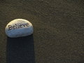 White affirmation stone a inscribed with the word believe throws a shadow on grey sand Royalty Free Stock Photography