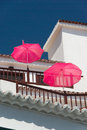 White balcony house with pink parasols on a background of blue sky Royalty Free Stock Photo