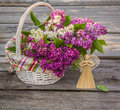 White basket with a branch of lilac and angel made ​​of stra Royalty Free Stock Photo