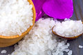 White bath salt in a wooden bowl with a spoon and an orchid Royalty Free Stock Photo