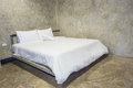 White bed with gray cement wall Royalty Free Stock Photo