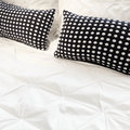 White bed linen with black cushions and polka dot Stock Image