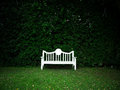 White bench in garden lush Royalty Free Stock Images