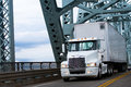 White Big rig semi truck and reefer on farm bridge Royalty Free Stock Photo