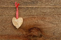 White birch love valentine s heart hanging on wooden texture bac with gingham ribbon natural cord and red clip rustic plywood Stock Image