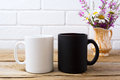 White and black mug mockup with chamomile and purple flowers in