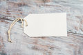 White blank tag with string on gray wooden background Royalty Free Stock Photo