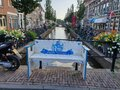 White blue bench on the Turfmarkt canal in the old town of cheese city Gouda in the Netherlands Royalty Free Stock Photo