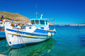 White-blue boat with Greek colors in bay, Greece Royalty Free Stock Photo