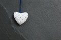 White Blue Dots Love Valentine's heart hanging on grey slate sto Royalty Free Stock Photo