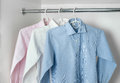White, blue and pink clean ironed men's shirts hanging on hanger Royalty Free Stock Photo