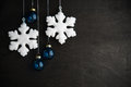 White and blue xmas ornaments on black wooden background. Merry christmas card. Royalty Free Stock Photo