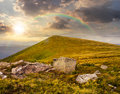 White boulders on the hillside at sunset composit landscape with sharp near mountain peak in light with rainbow Royalty Free Stock Photo