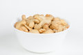 White bowl filled with roasted cashew nuts Royalty Free Stock Photos