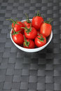 White bowl filled with small fresh tomatoes on grey background Royalty Free Stock Images