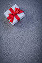 White boxed present with red knot on grey surface copyspace holi holidays concept Royalty Free Stock Photo