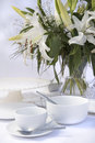White breakfast table setting with lily flowers bright crockery and flwoers Royalty Free Stock Images