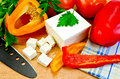 White brine cheese black knife parsley tomatoes red yellow bell pepper napkin wooden board Stock Images