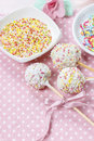 White cake pops on pink dotted table cloth colorful sprinkles in ceramic bowls Royalty Free Stock Image