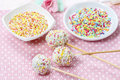 White cake pops on pink dotted table cloth colorful sprinkles in ceramic bowls Stock Image