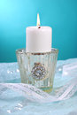 White candle with flame on blue background Royalty Free Stock Photography