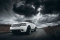 White car speed driving on road at dramatic clouds daytime Royalty Free Stock Photo